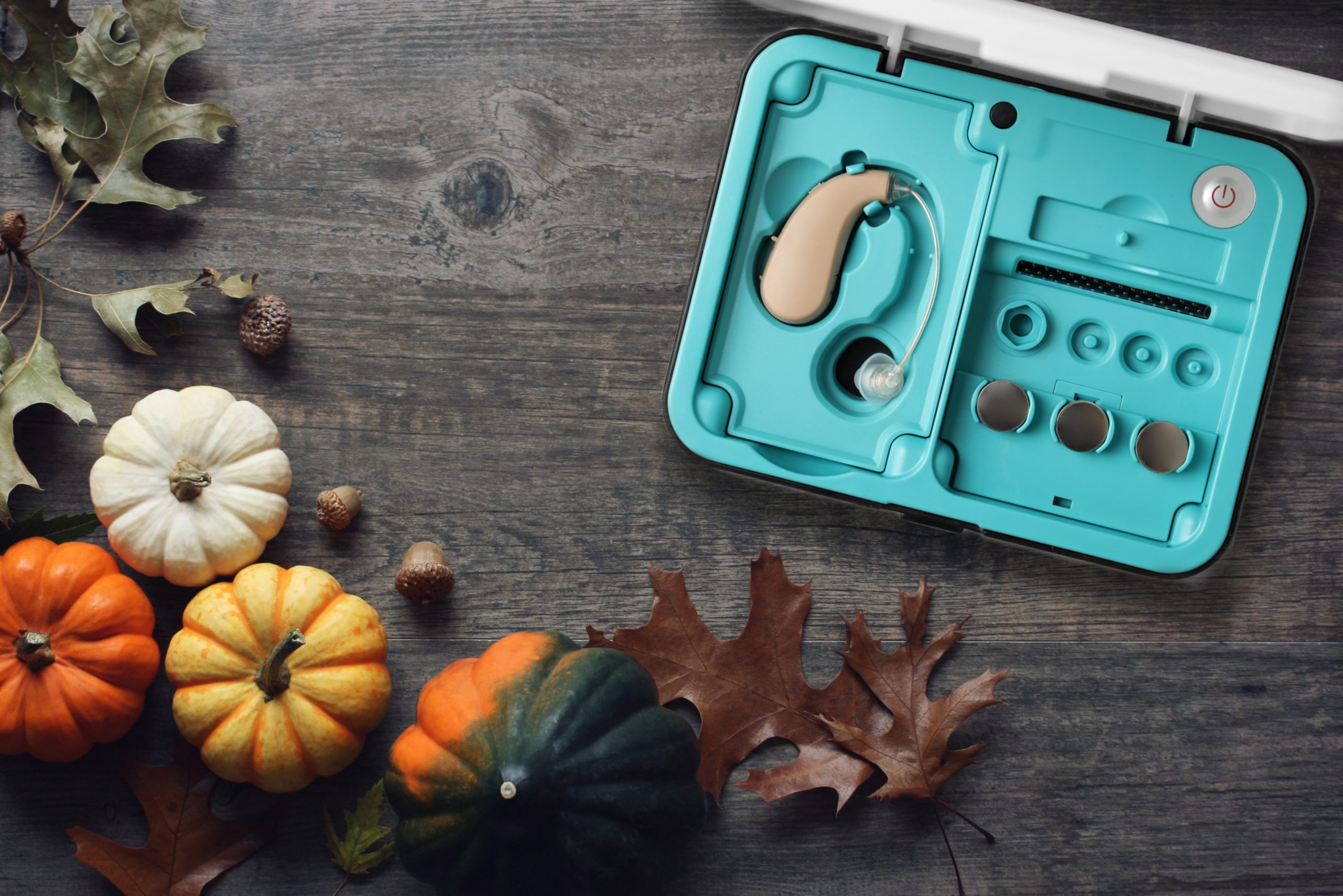 A hearing aid in its box on a table decorated for Thanksgiving.