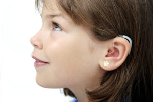 A young girl with a hearing aid looks upward off camera.