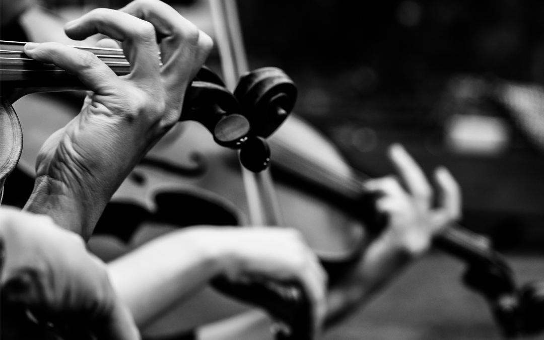 A black and white image of hands playing string instruments (a string quartet.)