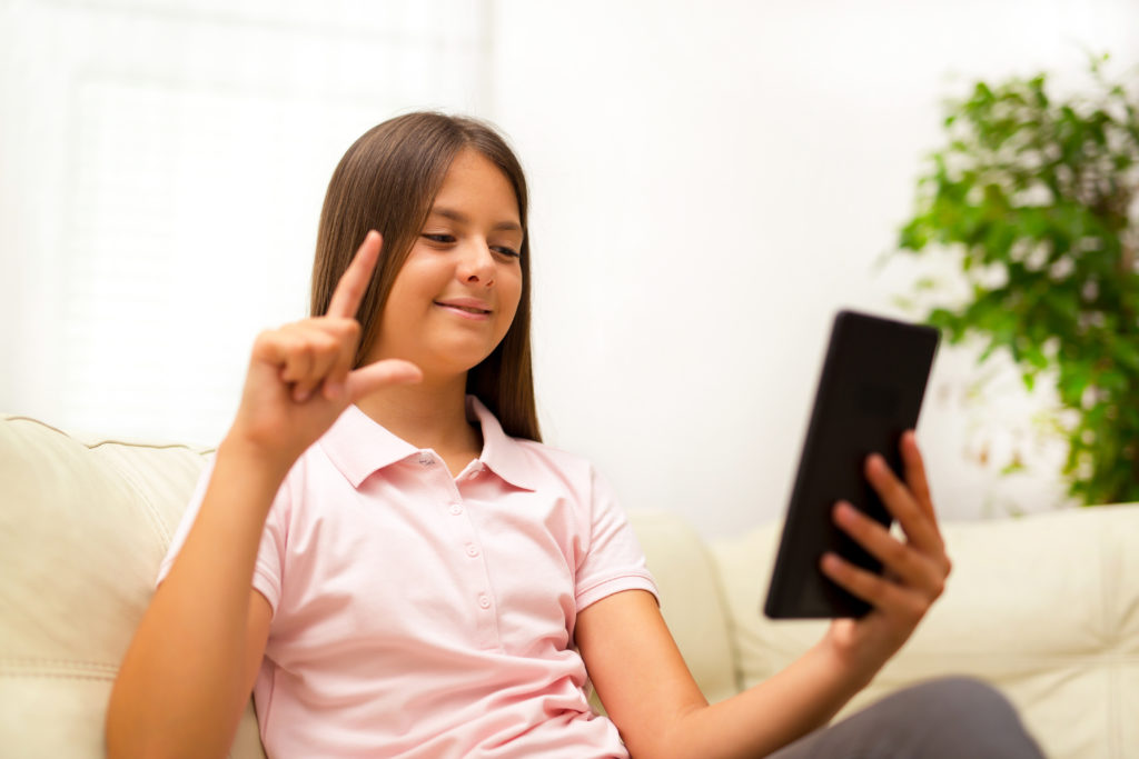 Young girl with fingers forming the letter L looking at smartphone