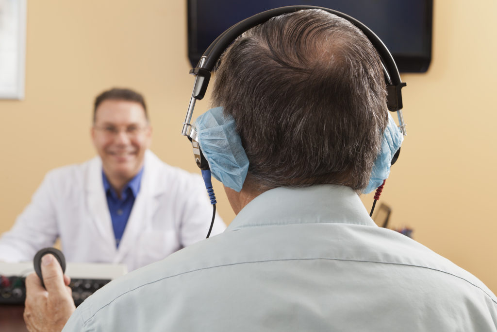 Gray-haired man getting a hearing test by an Audiologist