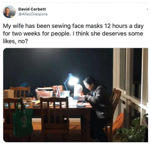 Woman making masks under lamp lighting when dark outside.